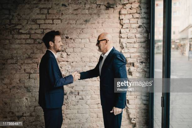 senior and mid-adult businessman shaking hands - successor stock pictures, royalty-free photos & images