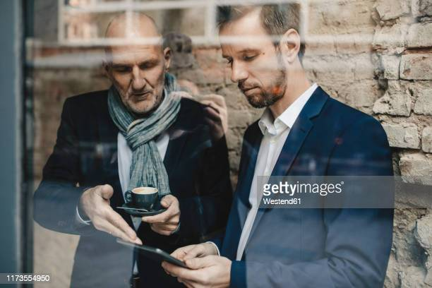 senior and mid-adult businessman sharing a tablet - successor stock pictures, royalty-free photos & images
