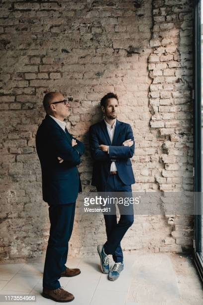 senior and mid-adult businessman standing at brick wall - successor stock pictures, royalty-free photos & images