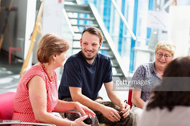 senior and young  adults, sitting, talking,using digital devicices