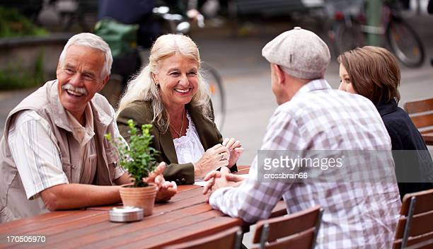 Senior and young couples laughing - sitting outdoors city scenery