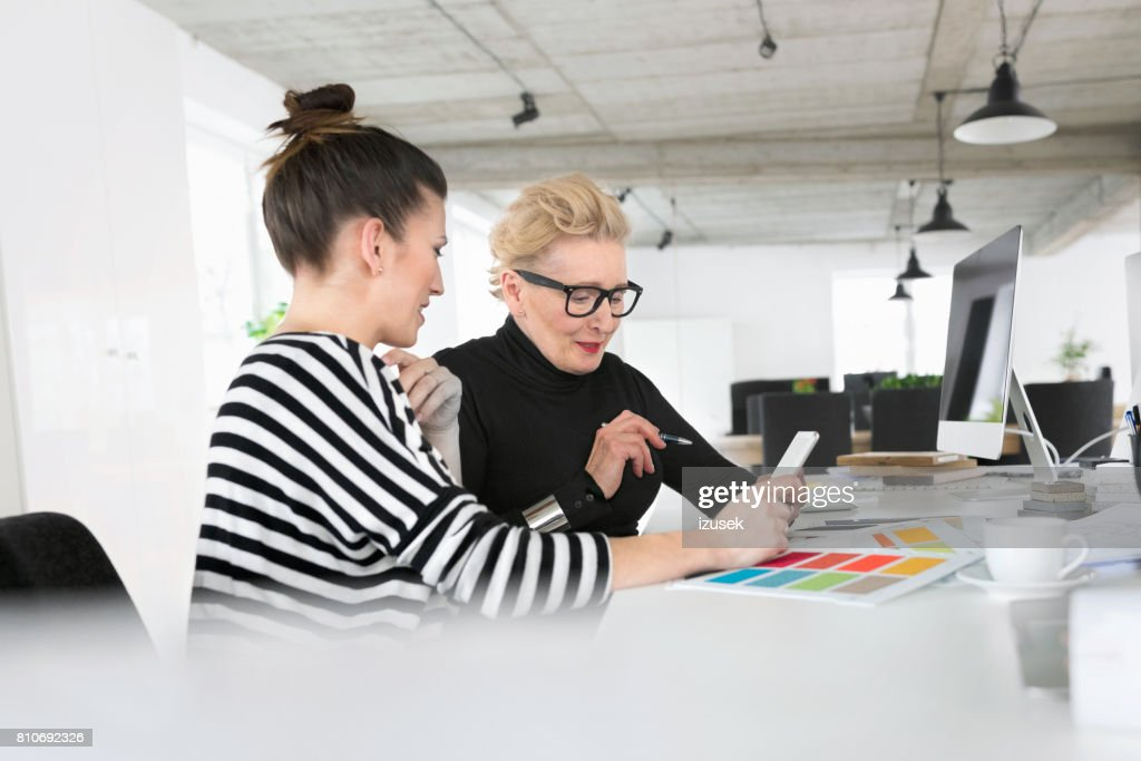 Senior And Young Interior Designers Using A Digital Tablet In The Studio Stock Photo