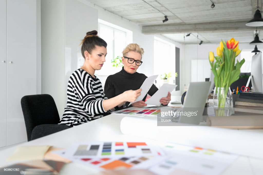 Senior And Young Interior Designers Working Together With Woman In The Office Stock Photo