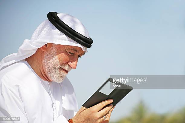 Senior Arab man looking at mobile phone