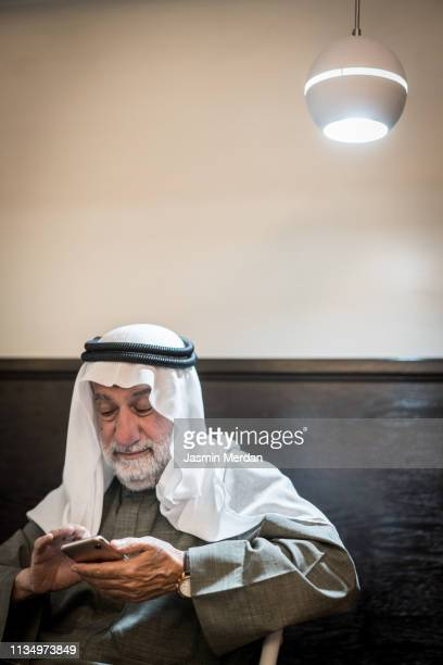 senior arab man with mobile phone - arab old man stock pictures, royalty-free photos & images