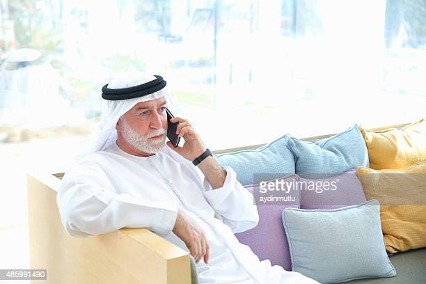 Senior Arabian man talking on phone