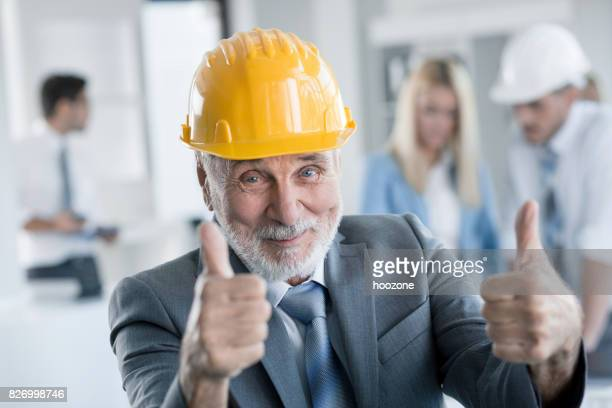 Senior architect showing thumbs up at office