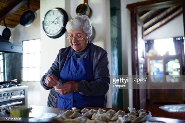senior argentinian woman preparing empanadas in her rural kitchen. - empanada stock pictures, royalty-free photos & images