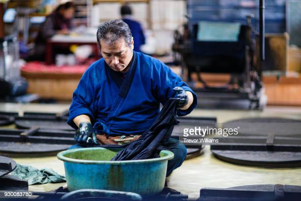 a senior artisan dyeing textiles with traditional indigo dye - japanese culture stock pictures, royalty-free photos & images