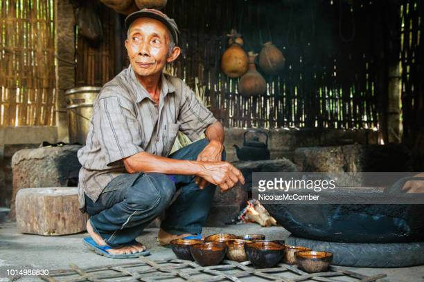 senior artisan indonesian palm sugar maker in kitchen looking away - balinese culture stock pictures, royalty-free photos & images