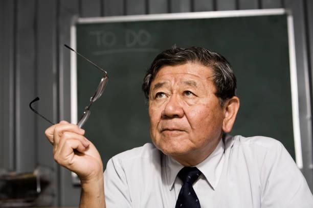 Senior Asian businessman holding eyeglasses