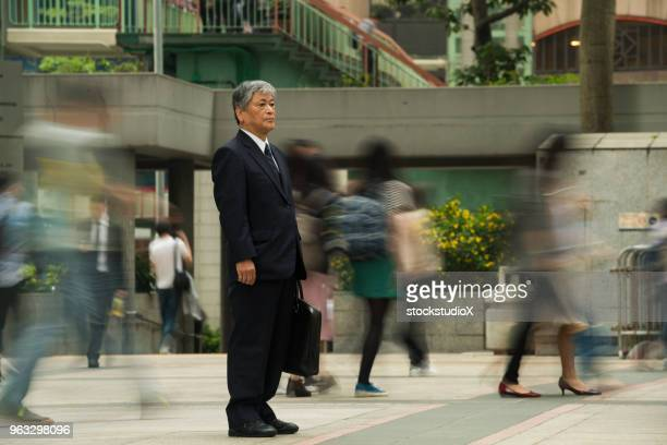 senior asian businessman standing out from the crowd - working seniors stock pictures, royalty-free photos & images