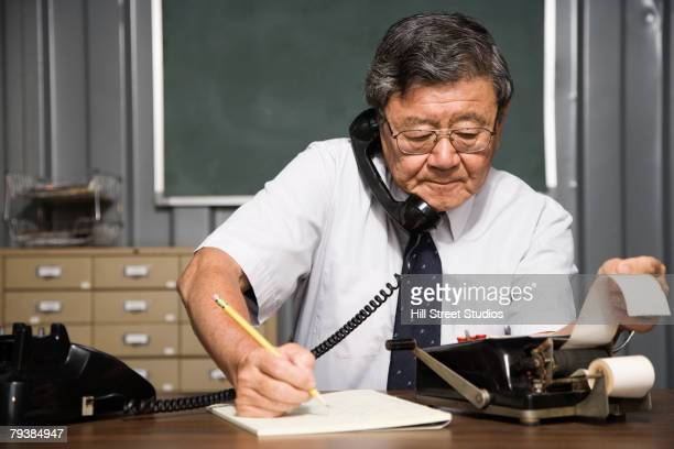 Senior Asian businessman using old fashioned adding machine