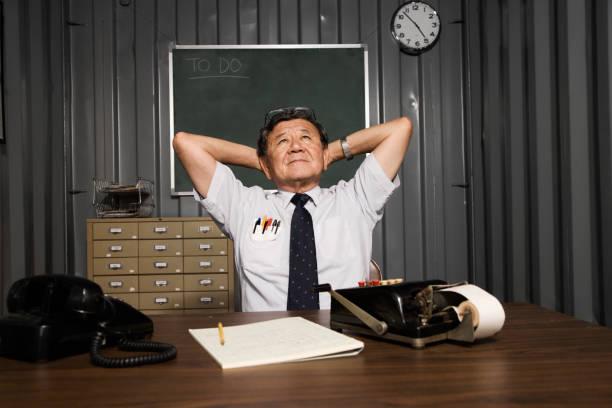 Senior Asian businessman with hands behind head