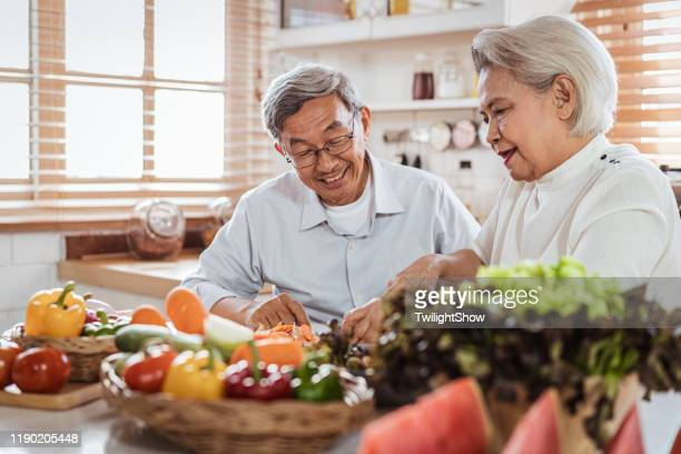 senior asian couple cooking together in kitchen - healthy eating stock pictures, royalty-free photos & images