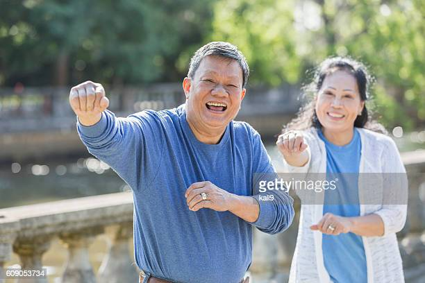 Senior Asian couple doing tai chi in park