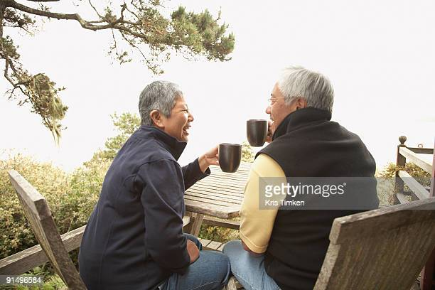 Senior Asian couple drinking coffee outdoors
