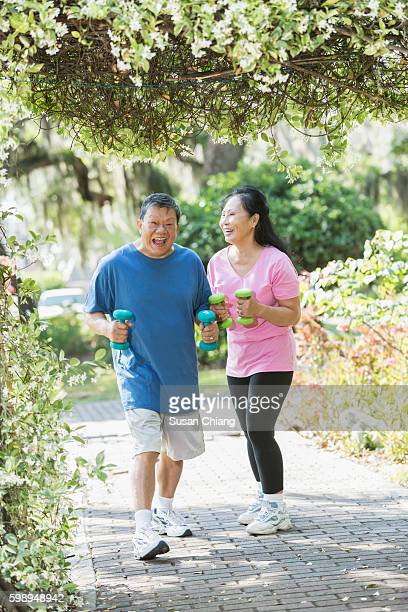 Senior Asian couple in park exercising together