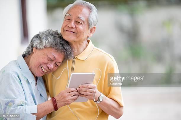 アジアの老人カップルの音楽を聞く