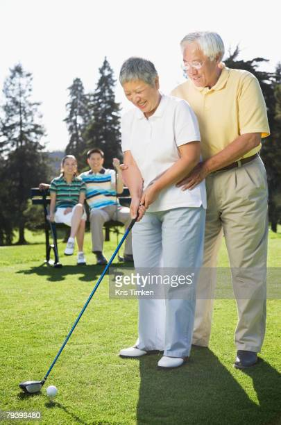 Senior Asian couple playing golf