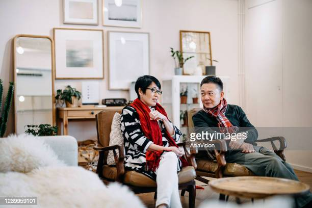 senior asian couple sitting on the armchair relaxing and having a conversation together at home - hong kong stock pictures, royalty-free photos & images