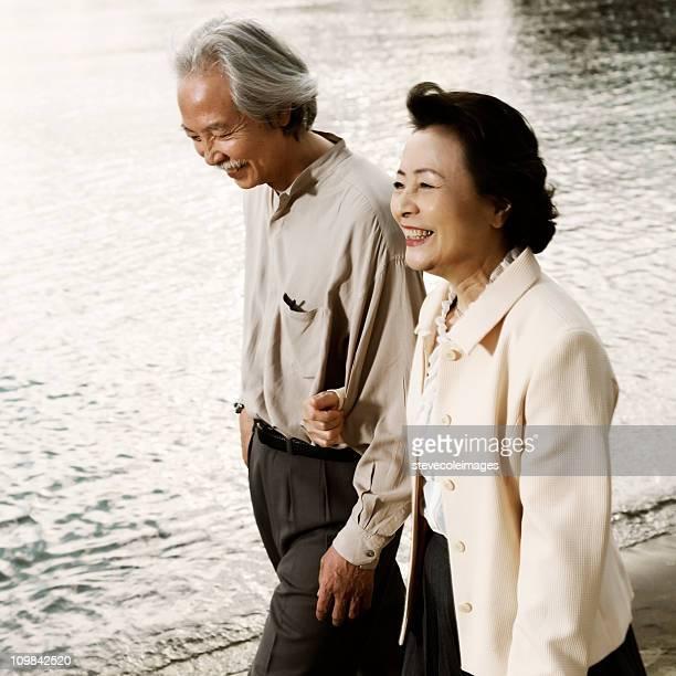 アジアの老人は、海岸に沿って歩くカップル