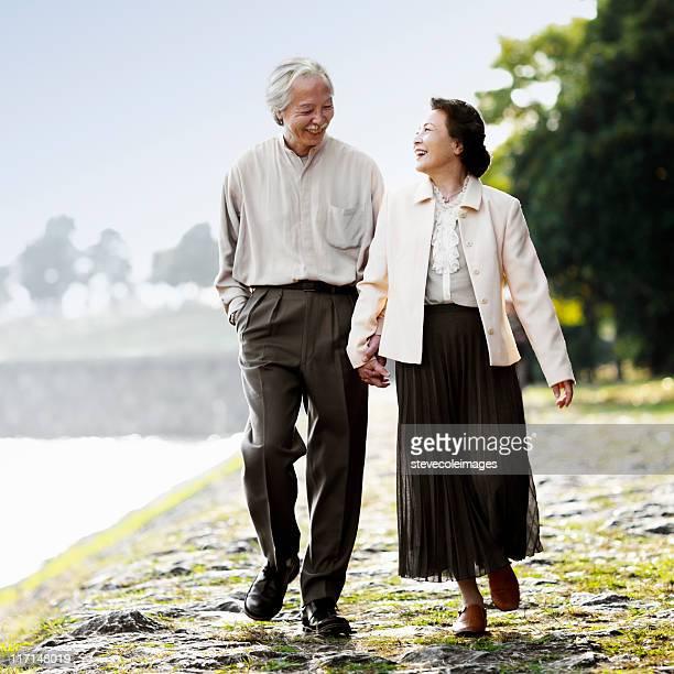Senior Asian Couple Walking on the  Rocky Beach