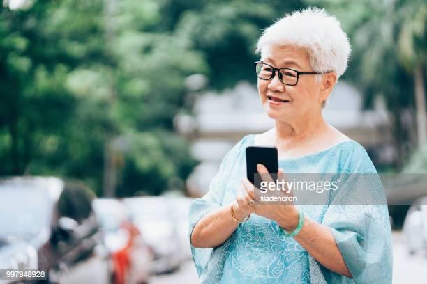 Femme Senior Asian ethnicity dans la ville à l'aide de téléphone intelligent