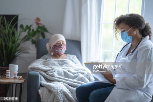 senior asian female cancer patient wearing mask talking to doctor - cancer illness stock pictures, royalty-free photos & images