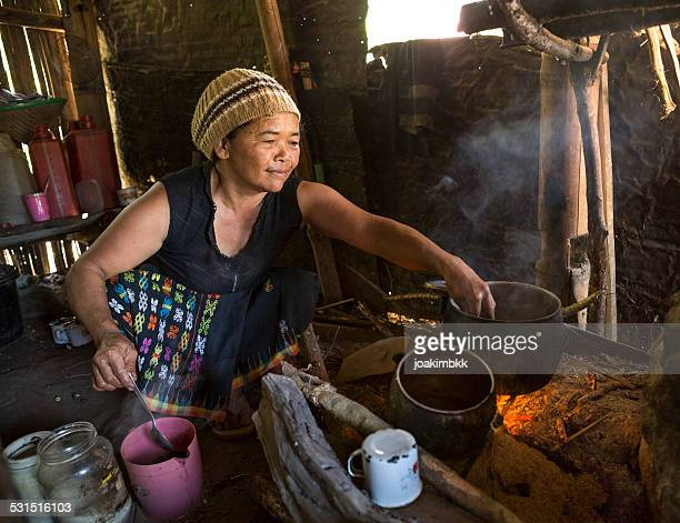Senior Asian lady cooking with wood fire