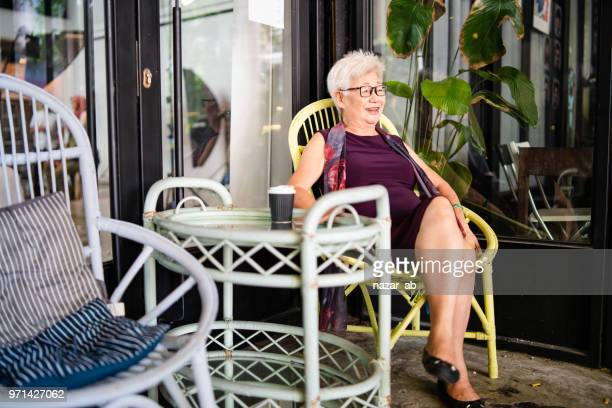 Senior asian lady relaxing in retirement village.