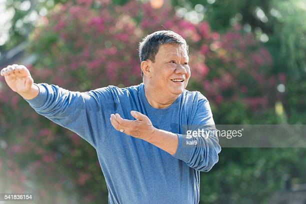 Senior Asian man doing tai chi