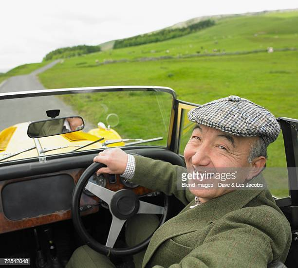 Senior Asian man driving old fashioned sports car in countryside