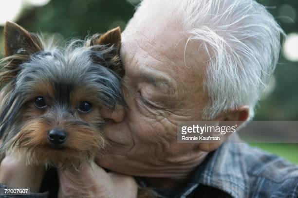 Senior Asian man hugging small dog