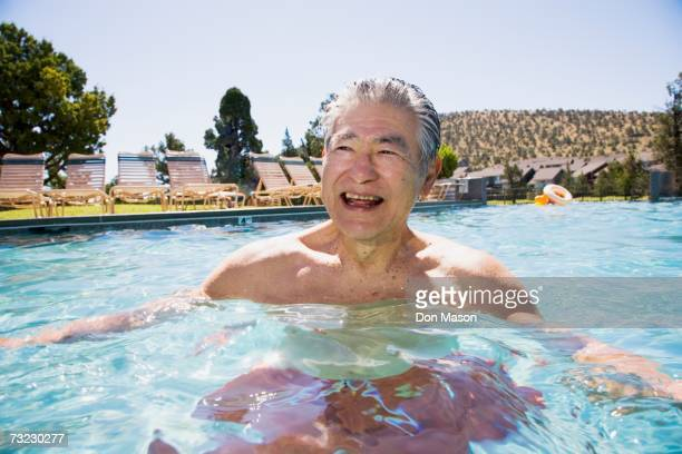 Senior Asian man laughing in swimming pool