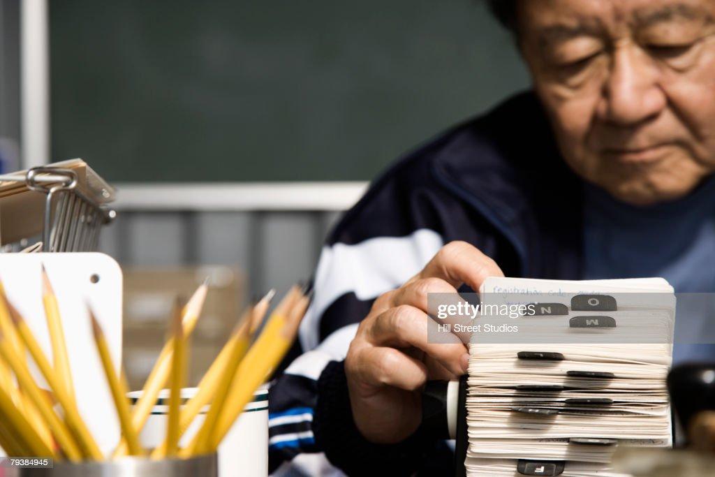 Senior Asian man looking at circular card file : Stock Photo