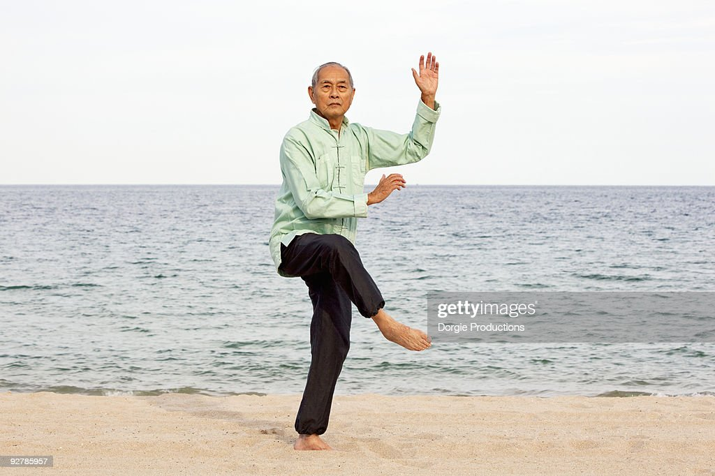 Senior Asian man practicing Tai Chi on beach : ã¹ããã¯ãã©ã
