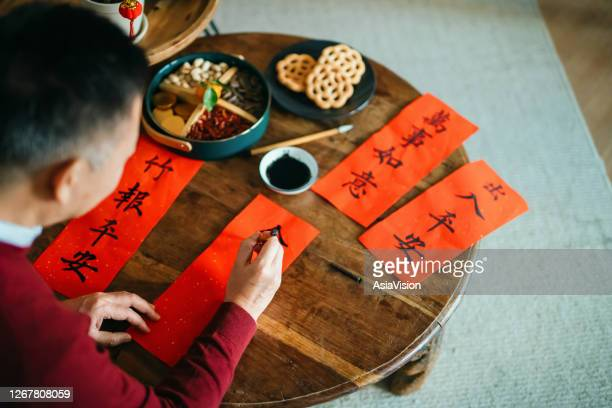 senior asian man practising chinese calligraphy for chinese new year fai chun (auspicious messages) and writing it on a couplets at home - chinese new year stock pictures, royalty-free photos & images