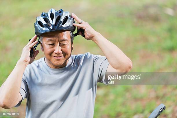 Senior Asian man putting on bike helmet