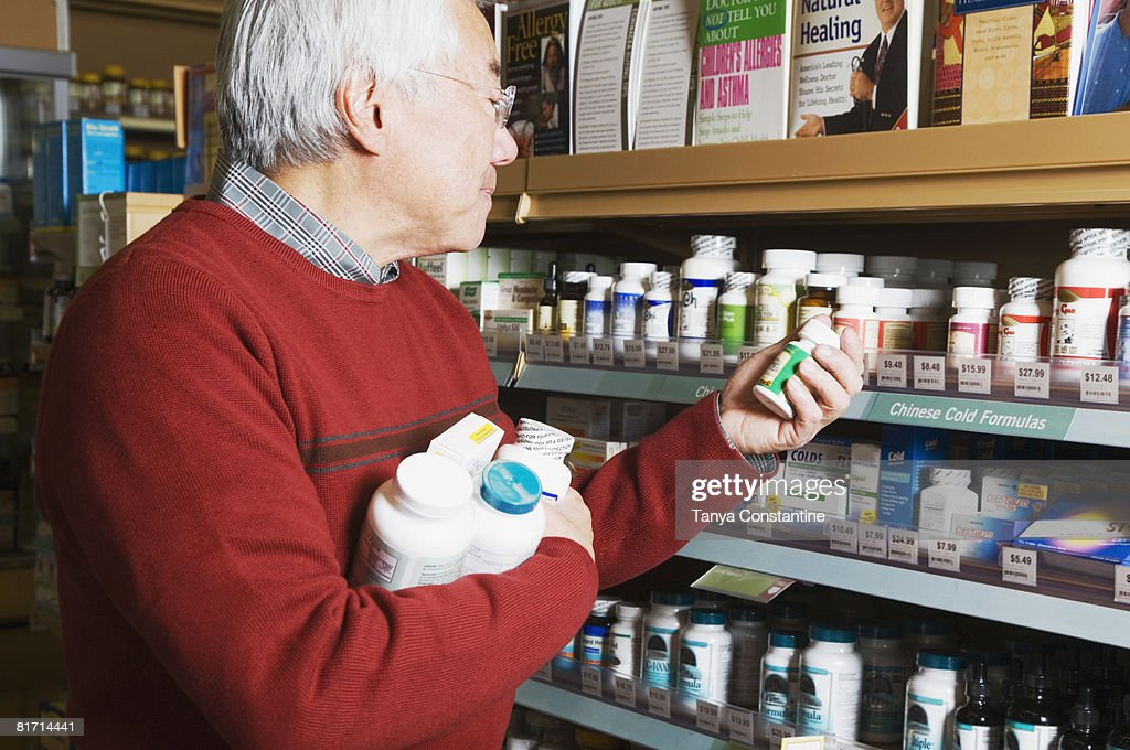 Senior Asian man shopping for natural medicine : Stock Photo