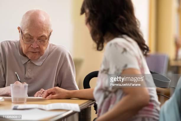 Senior Asian Man Signing Document with Financial Advisor