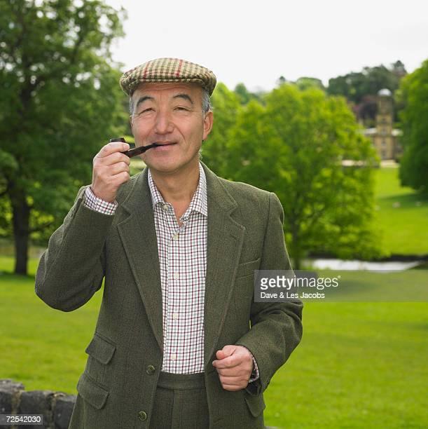 Senior Asian man smoking pipe outdoors