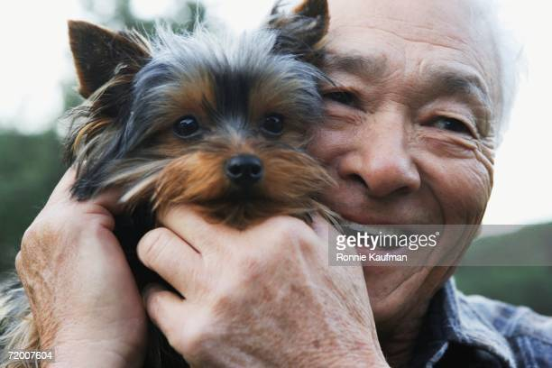 Senior Asian man with small dog