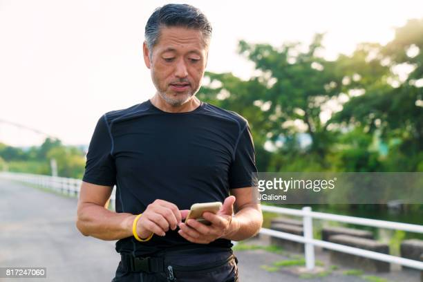 senior asian runner pausing to check his smartphone - japanese old man stock pictures, royalty-free photos & images