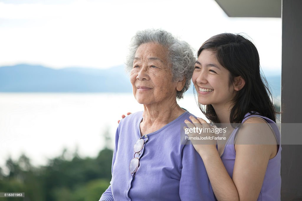 Senior Asian Woman and Granddaughter Enjoying View from Balcony : Stock Photo