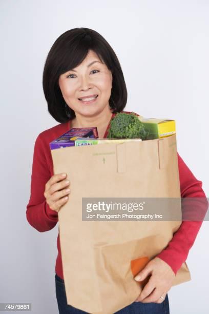 Senior Asian woman carrying grocery bag