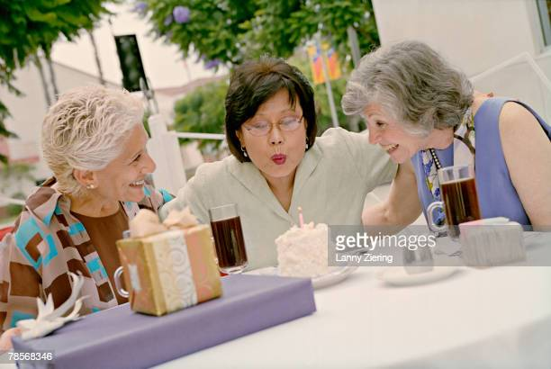 Senior Asian woman celebrating birthday with friends