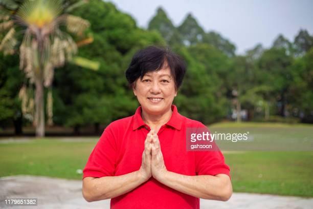 senior asiatisk kvinna i en välkommen pose, hälsning med thailändsk kultur sawasdee - prayer pose greeting bildbanksfoton och bilder