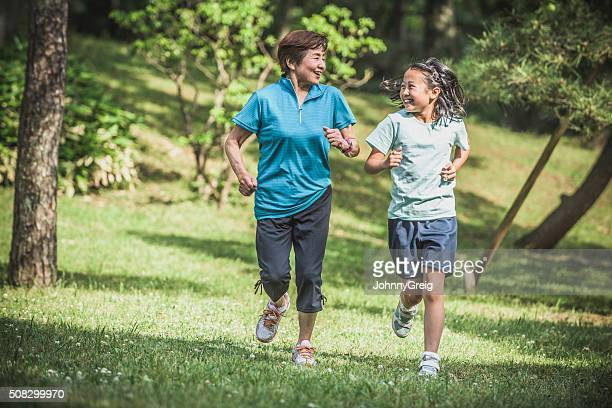 Senior Asian woman jogging with her granddaughter in park