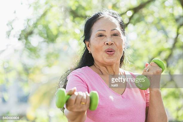 Senior Asian woman lifting handweights